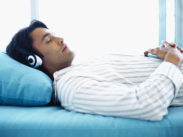 Person using binaural beats to sleep in bed with headphones
