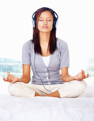 Person meditating while listening to binaural beats