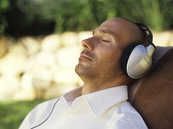 Man With Headphones Laid Listening To Binaural Beats